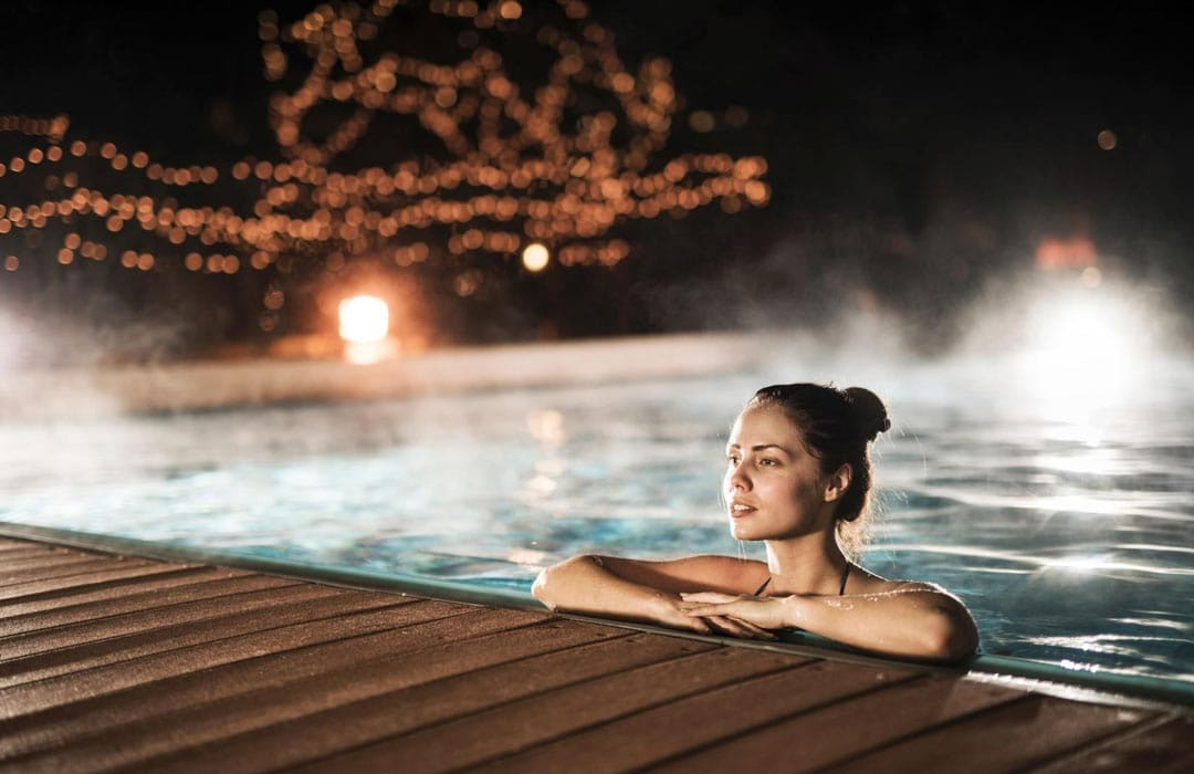 A woman enjoying a swim with our inverter pool heat pumps